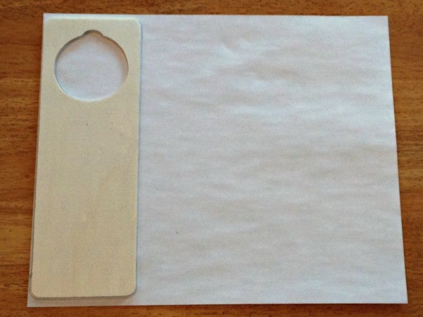 a wooden door hanger on a piece of paper ready to be traced