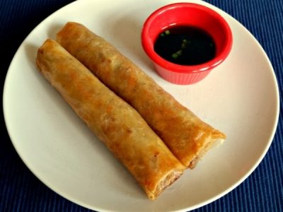 Lumpia on white place with sauce for dipping in little red bowl