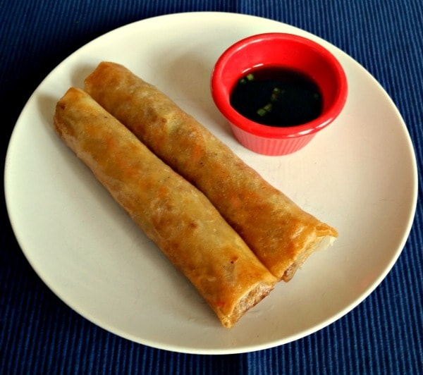 two Lumpia next to a red bowl of sauce on a white plate on a dark blue cloth