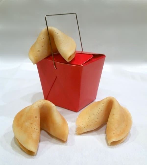 three homemade fortune cookies and a small red chinese take out food box on a white counter
