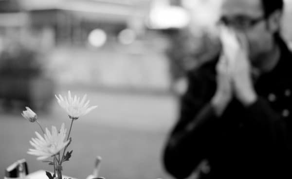 blurred black and white photo of a person blowing their nose standing near flowers