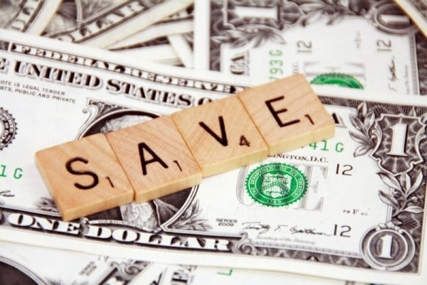 dollar bills with scrabble wood pieces spelling out the word save on top of them
