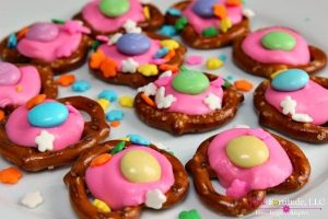 pretzels decorated with pink frosting and candies to look like Bunny Buttons for an Easter recipe
