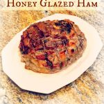 a whole ham on a white platter on a kitchen counter with title text reading Honey Glazed Ham