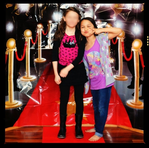girls posing for a picture in front of a backdrop of a Red Carpet