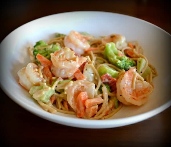 Shrimp Primavera in a white dish on a dark brown table