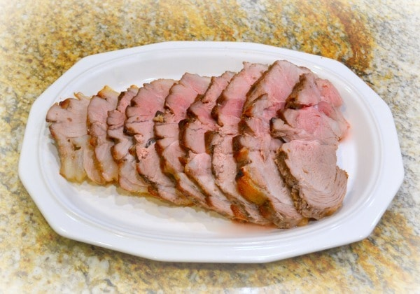 Sliced Ham on a white platter on a kitchen counter