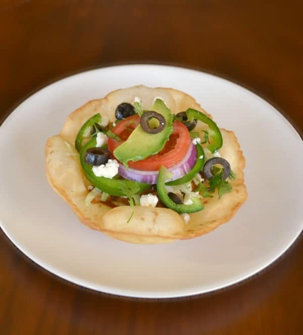 Chicken Tostada on a white plate on a brown table