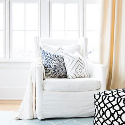 White chair with decorative pillows and black and white poof
