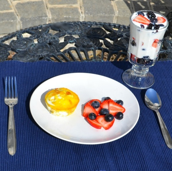 White plate with breakfast casserole cup, strawberries, and blueberries. Glass dish with fruit parfait. Fork and spoon. All on blue place mat