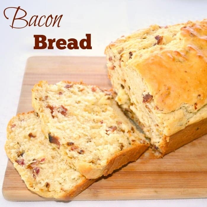 two slices of bacon bread next to the rest of the loaf on a wooden board with title text reading Bacon Bread