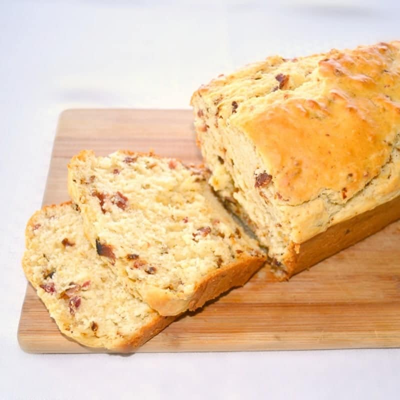 Bacon Bread loaf, some of it sliced, on a wooden board