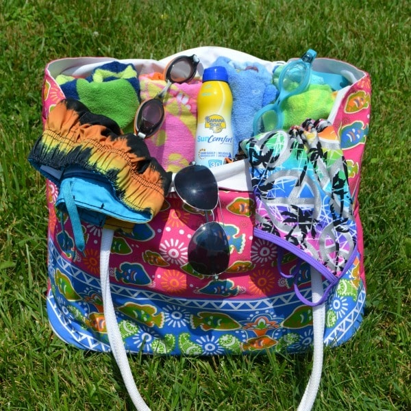 Banana Boat SunComfort Clear UltraMist Sunscreen in a swim bag on the grass