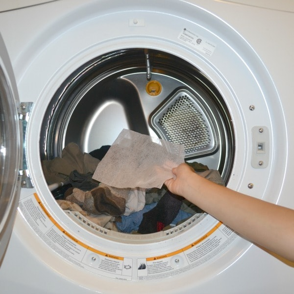 Putting dryer sheet into dryer full of clothes