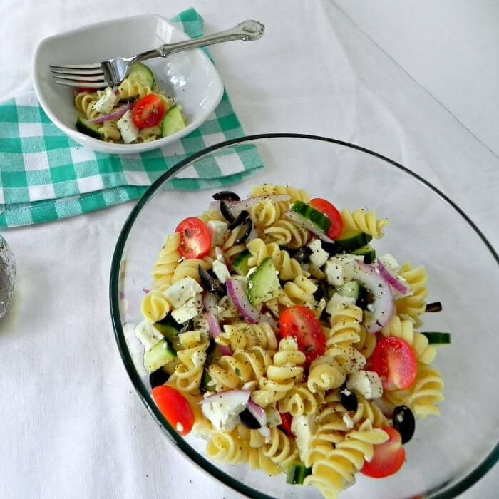 Greek-Pasta-Salad in a glass bowl and in a white dish with a fork in it