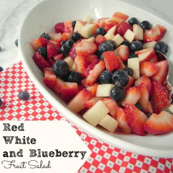 a fruit salad in a white dish on a red and white checkered cloth with title text reading Red White and Blueberry Fruit Salad