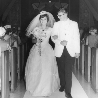Black and white picture of bride and groom walking down the isle of a church
