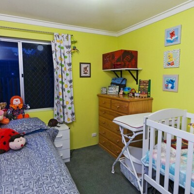 Kids bedroom with yellow walls, twin bed, crib, and wood dresser