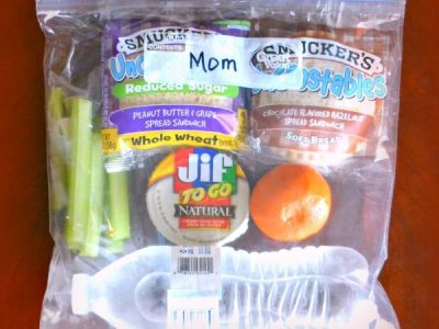 Bag of snacks. Orange, celery, Jif togo, smuckers, bottle of water