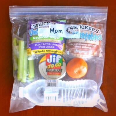 Bag of snacks. Orange, celery, Jif togo, smuckers, bottle of water