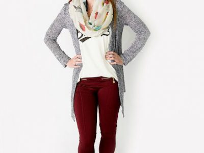 Woman wearing red pants, black boots, white shirt, grey cardigan, and scarf