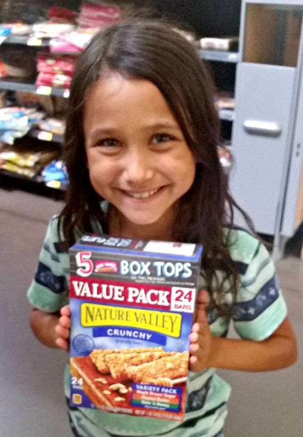 a girl holding a box of Granola Bars with Box Tops on them