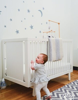 Star stickers on wall behind white crib with baby standing against it