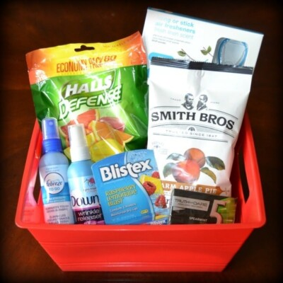 Red plastic bucket with cough drops, air freshener, candy, gum, chapstick, frebreze spray, and wrinkle release spray