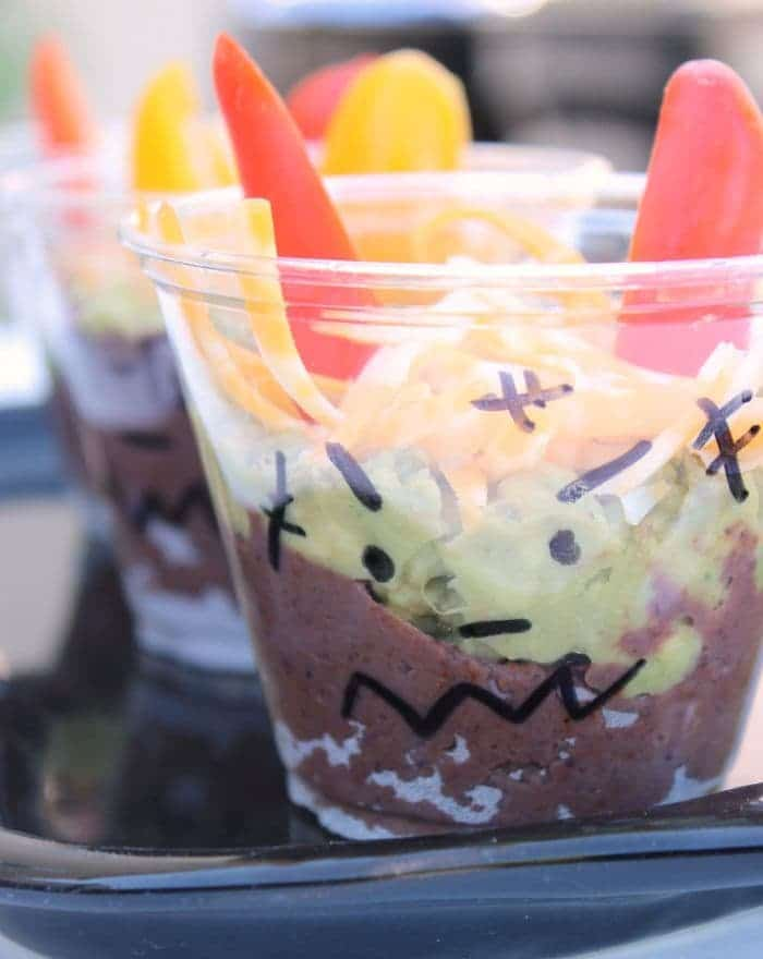 bean dip in plastic cups decorated to look spooky