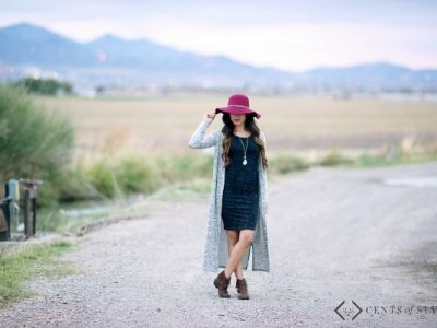 Woman styling black dress, grey cardigan, and pink hat