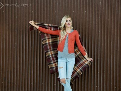 Woman with blonde hair styling a plaid blanket scarf