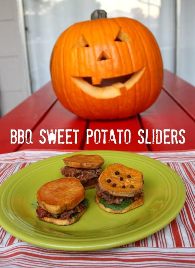 Bbq sweet potato sliders on a green plate on a red and white cloth on a red table with a jack-o-lantern in the background