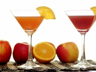 An orange cocktail and a red cocktail with oranges and apples in the background