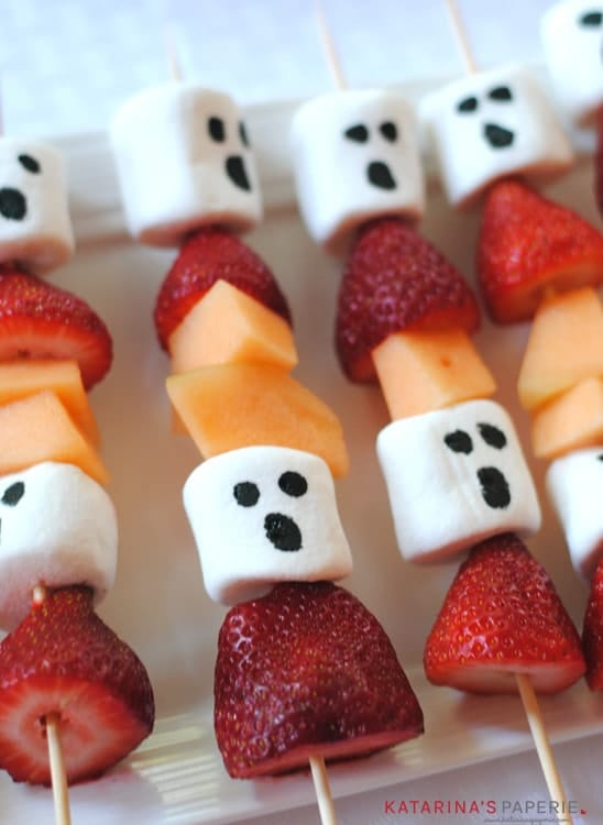 cabobs made with strawberries, cantaloupe, and marshmallows decorated to look like ghosts