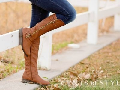 Light brown boots being styled in front of white fence