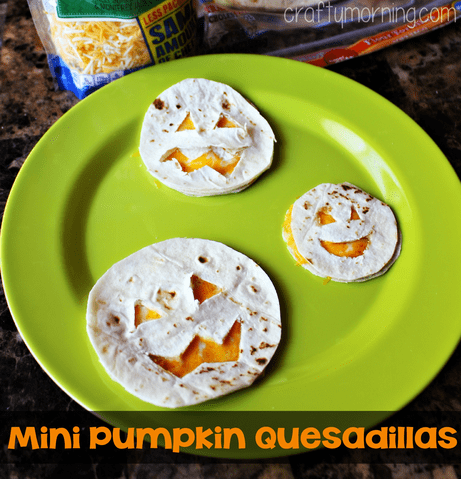 cheese quesadillas cut out to look like jack-o-lanterns on a green plate with text reading Mini Pumpkin Quesadillas