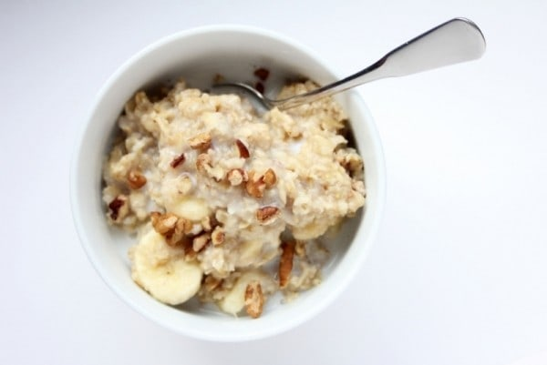 overhead view of oatmeal and a spoon in a white bowl on a white background