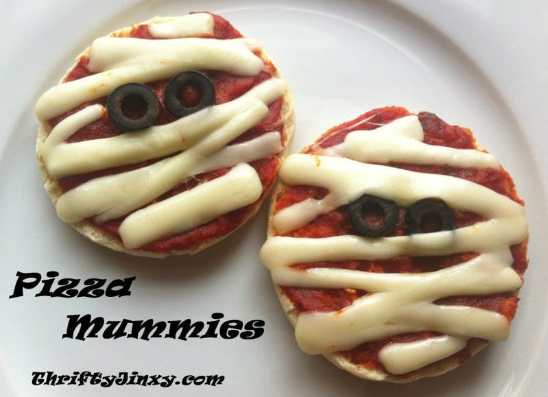 pizzas covered with sauce, cheese and olives to look like mummies