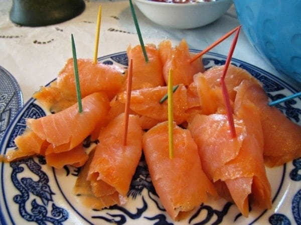 Salmon rolled up with toothpicks in it on a blue and white plate