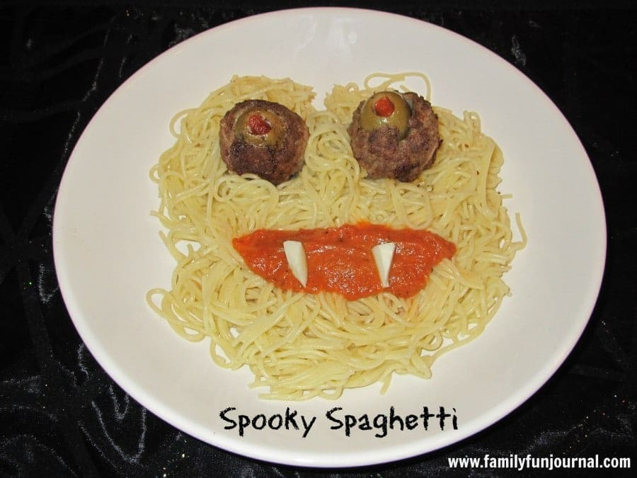 Spaghetti noodles with sauce, cheese, meatballs and olives on it arranged to look like spooky spaghetti on a white plate on a black background