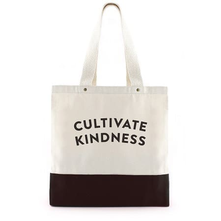 a white and black tote bag with text on it reading Cultivate Kindness