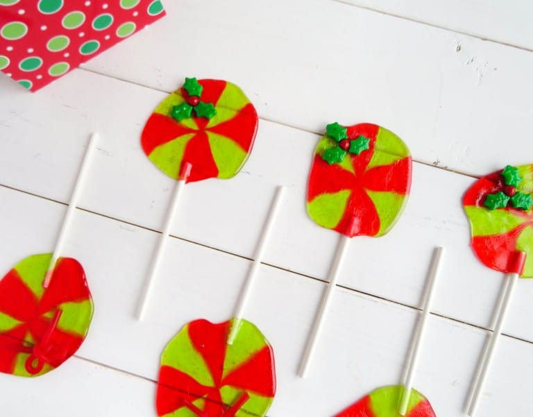 jolly rancher Christmas wreath suckers on a white wood table next to a present