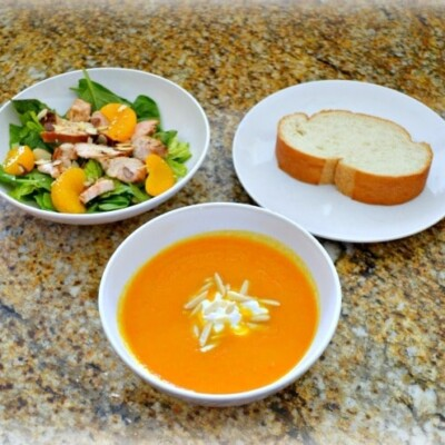 Bowl of soup, bowl of salad, and plate with slice of bread