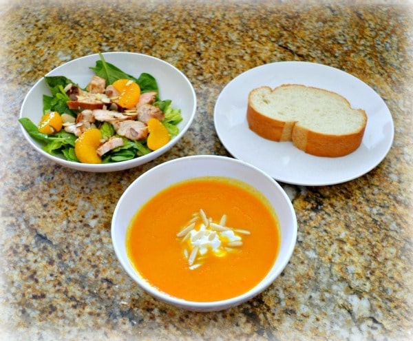 ginger carrot soup and asian chicken salad in white bowls next to a slice of bread on a plate, all on a kitchen counter