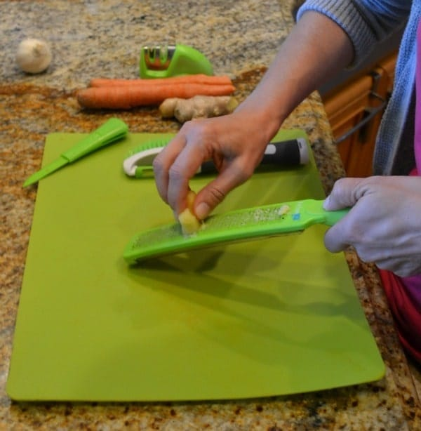 a lady mincing Garlic using a special tool on a green mat on a kitchen counter