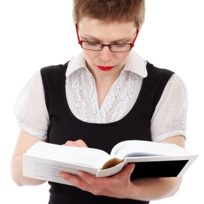Woman with red glasses reading a large book