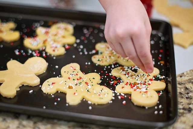 a person putting sprinkles on sugar cookies on a baking sheet