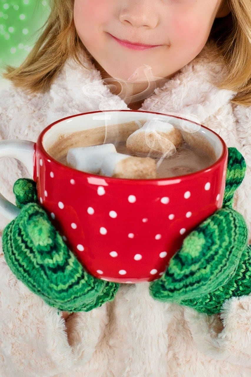 a girl wearing a fuzzy white jacket and green mittens holding a big red and white polka dotted mug of hot chocolate