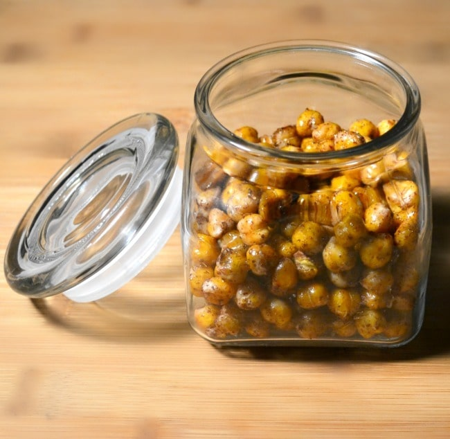 Honey Roasted Chickpeas in an open glass jar on a brown table