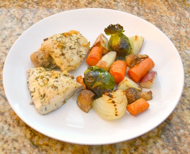 oven roasted chicken and vegetables on a white plate on a brown counter